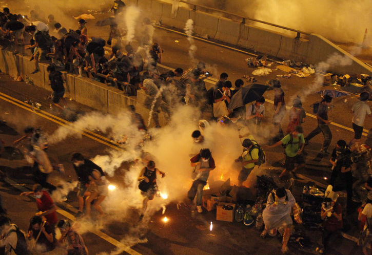 Riot police fire teargas to disperse protesters after thousands of demonstrators blocked the main street to the financial Central district outside the government headquarters in Hong Kong September 29, 2014.  [REUTERS]