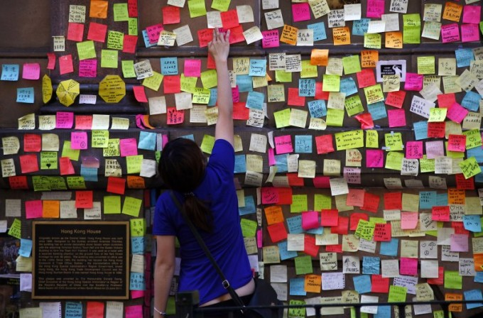 A woman places a piece of paper with a message of support for pro-democracy protesters in Hong Kong next to hundreds of others outside of the Hong Kong House in central Sydney October 5, 2014. [Reuters]