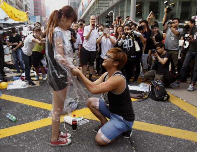 Yau, 22, gets down to his knees and proposes to his girlfriend Chen, 21, both university students and pro-democracy protesters. on a main street which they occupied, at Mongkok shopping district in Hong Kong October 5, 2014. [Reuters]