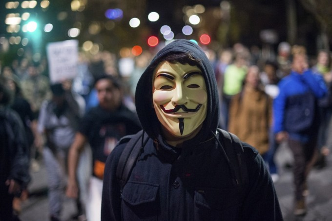 A protester wears a Guy Fawkes mask while marching against police violence in Berkeley, California December 10, 2014.  REUTERS/Noah Berger