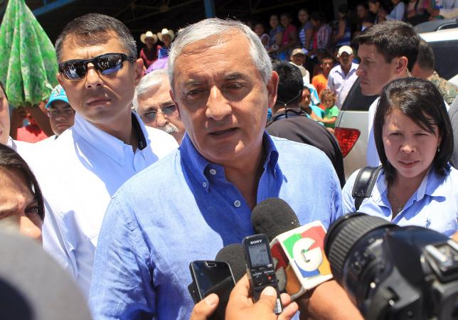Guatemalan President Otto Perez Molina talks to reporters after an event in Zacapa, in this handout photograph released to Reuters by the Guatemala Presidency on August 21, 2015.