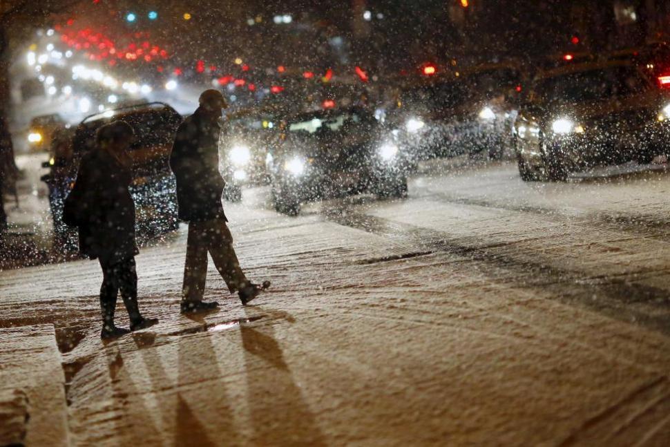 People cross a street as it snows in DC, Jan. 20, 2016. REUTERS