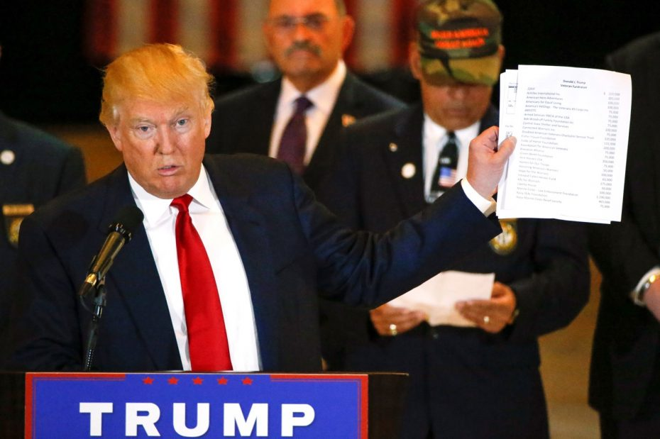 """Donald Trump holds paperwork which states """"Donald J. Trump, Veteran Fundraiser"""" in New York, U.S., May 31, 2016.  REUTERS"""
