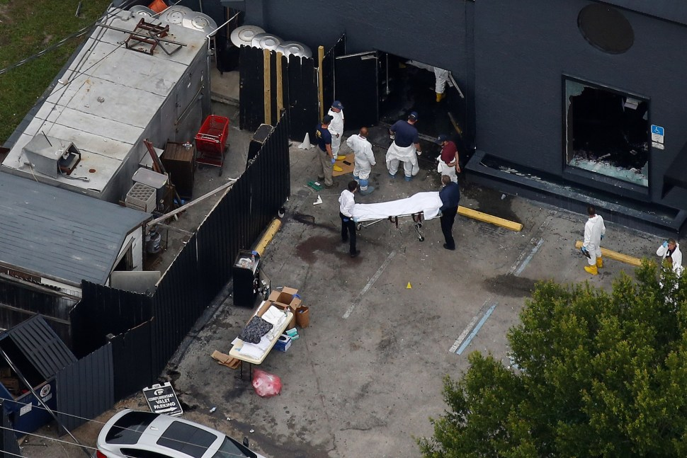 Investigators work the scene following a mass shooting at the Pulse gay nightclub in Orlando Florida,  June 12, 2016. REUTERS/Carlo Allegri