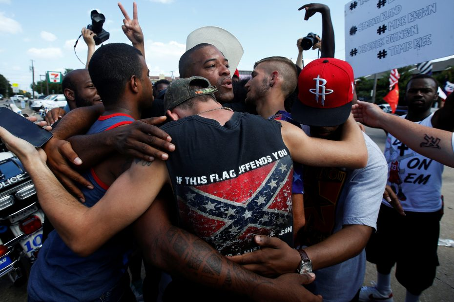 People, including a man wearing a confederate flag, hug after taking part in a prayer circle after a Black Lives Matter protest following the multiple police shootings in Dallas, Texas, U.S., July 10, 2016.  REUTERS/Carlo Allegri
