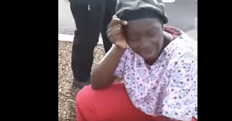 A woman identified as the victim's sister sits on a curb, in shock, as the ambulance carrying her brother leaves without her.