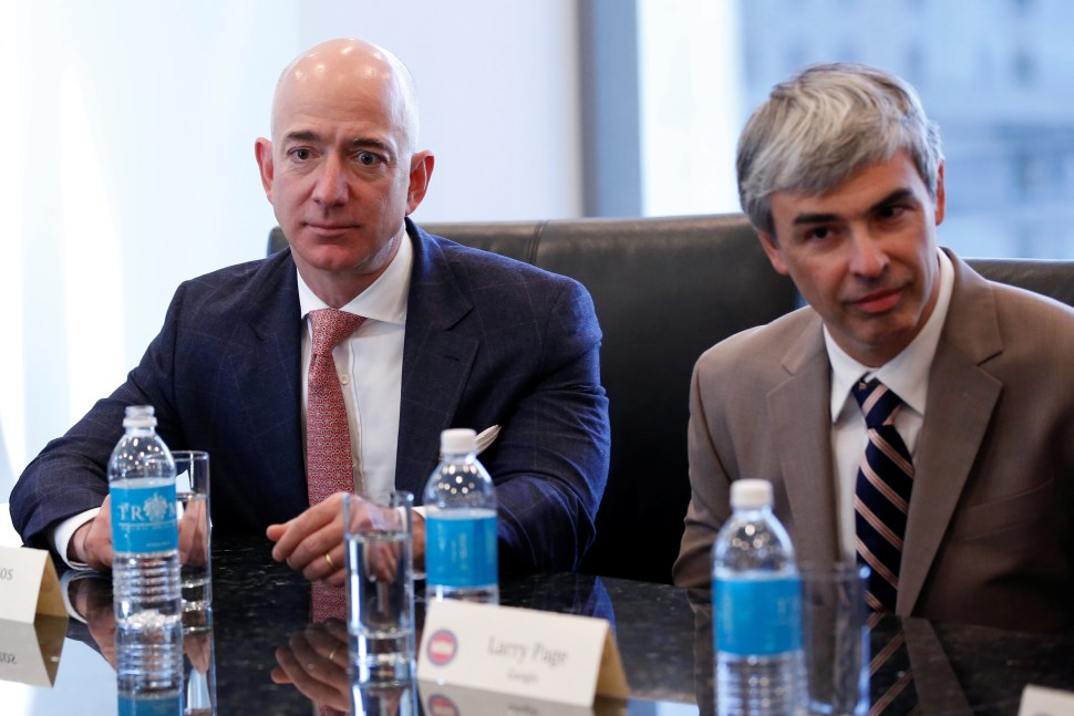 (L-R) Amazon CEO Jeff Bezos and Larry Page, CEO and Co-founder of Alphabet, sit during a meeting with U.S. President-elect Donald Trump and technology leaders at Trump Tower in New York, U.S., December 14, 2016. REUTERS