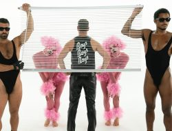 two studs hold up blinds in front of pink poodle humanoids and seth bogart