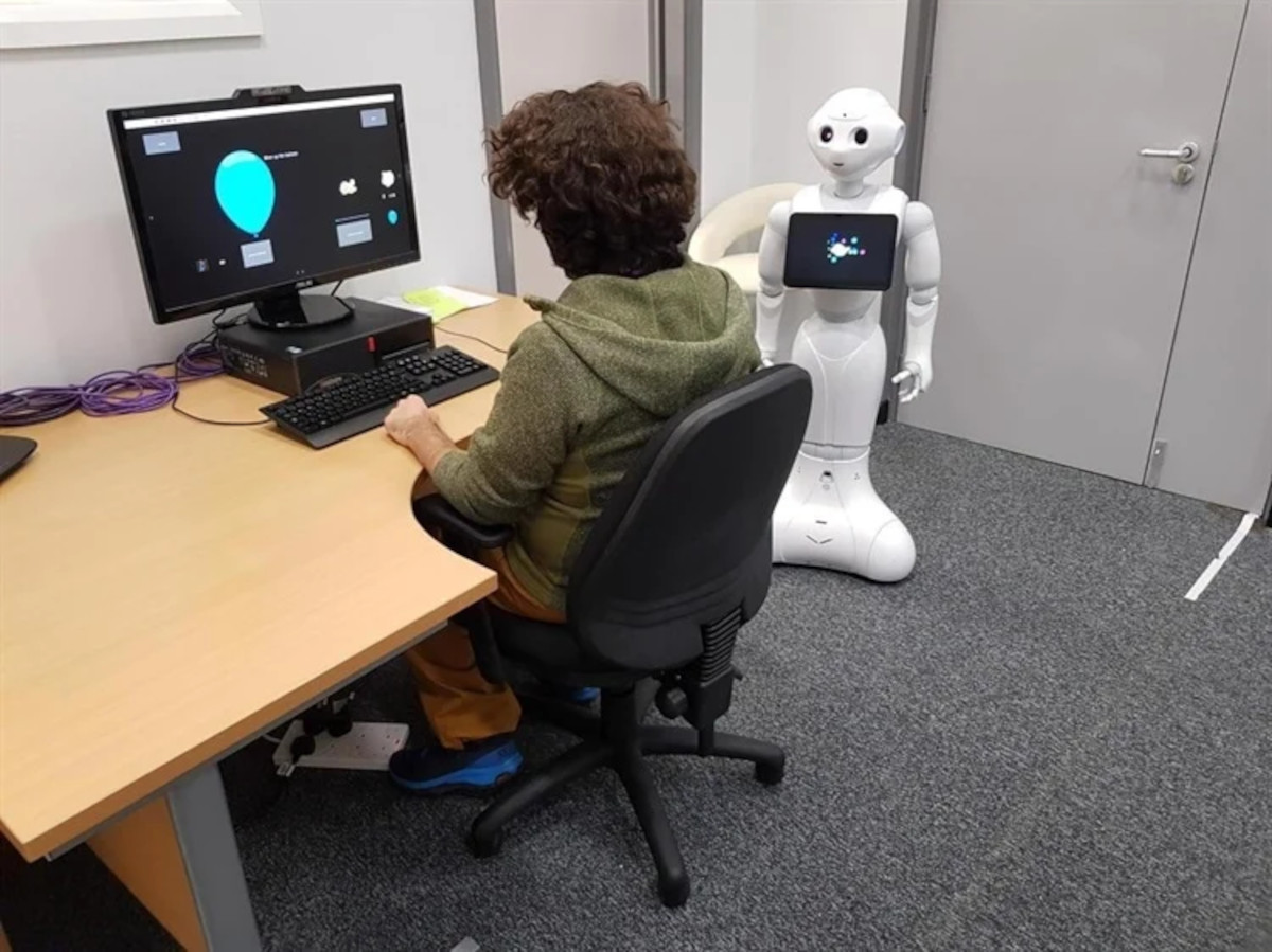 Image of Pepper robot interacting with a subject at a computer