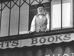 Black and white photo of Lawrence Ferlinghetti upstairs at City Lights Books