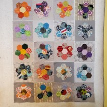 colorful hexi quilt blocks on the design wall