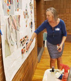 woman arranging quilt blocks