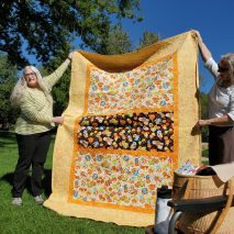 woman holding yellow quilt in the park