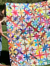 woman holding up bright color quilt