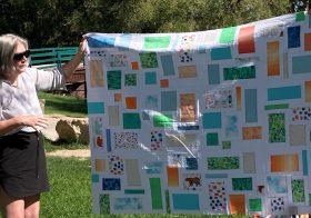 woman holding up quilt