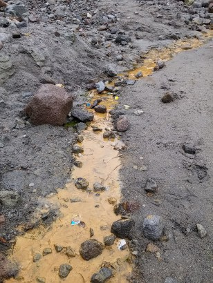 Ground rich in iron oxide, responsible for the rust-orange color of water