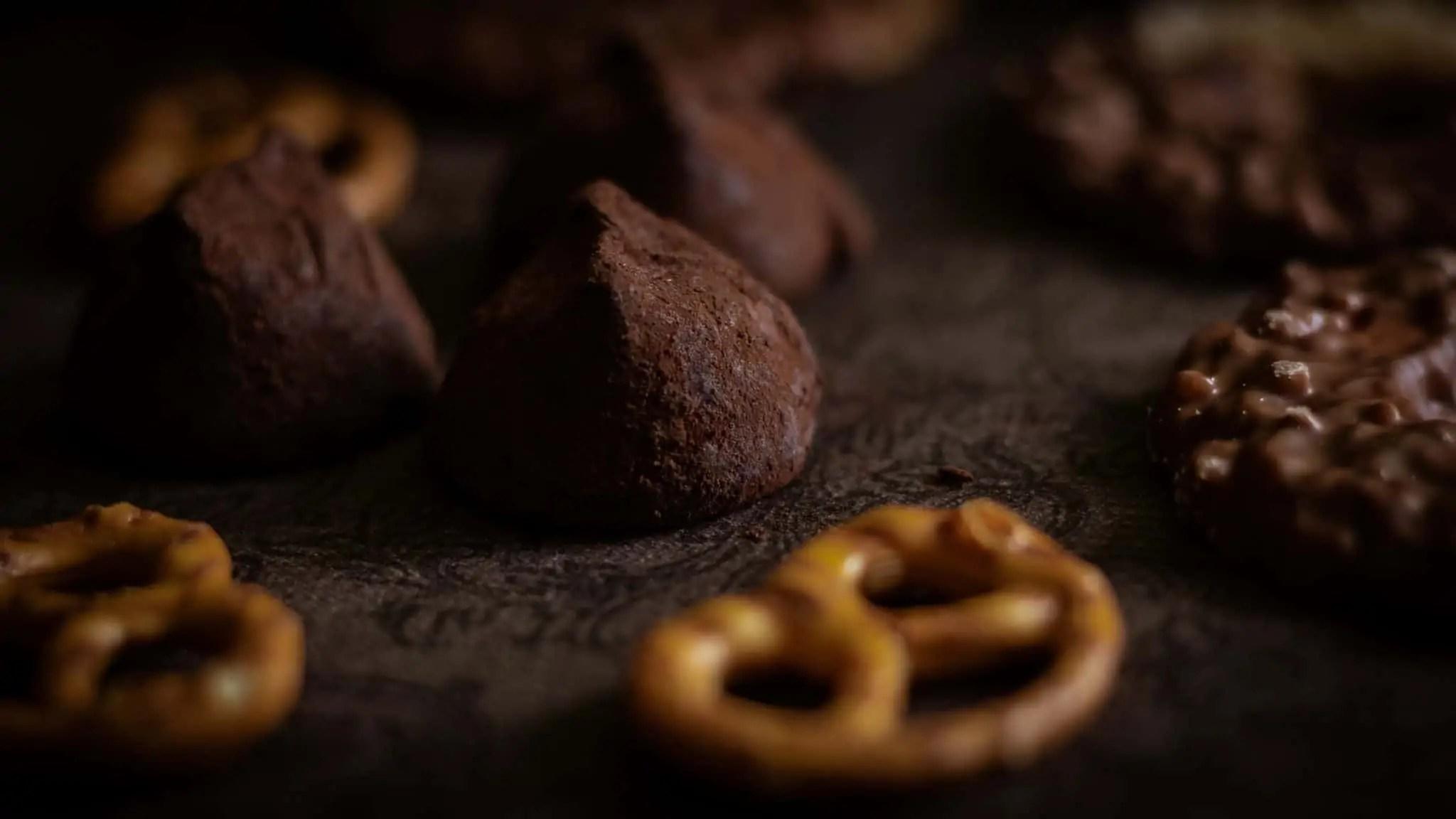 Czarna fotografia jedzenia czekolada precelki i ciastka 5 scaled - Czarna fotografia jedzenia