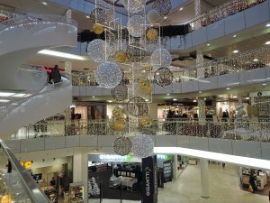 Multi-level mall decorated with Christmas lights on the railings with different sizes of transparent balls encased in lights dangling from the ceiling.