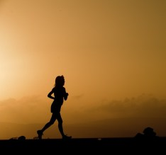 silhouette of a woman running at sunset in a wide open area