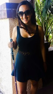 Chrissy is standing with her purple (white) cane posing for the camera