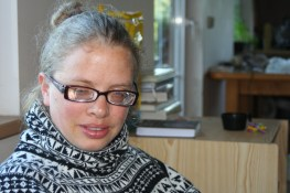 In this portrait of Arie she is wearing dark framed eyeglasses and a black & white geometric print turtleneck sweater. Her hair is pulled back into a bun.