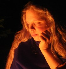 Head shot of Arie facing left, her cheek resting on her hand looking pensive. The lighting is a soft glow against a black background as if from a campfire.