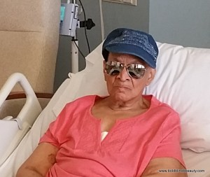 Mom is wearing a denim cap embellished with rhinestones, aviator sunglasses and a coral top as she sits in her hospital bed prepared for transportation to the nursing facility.