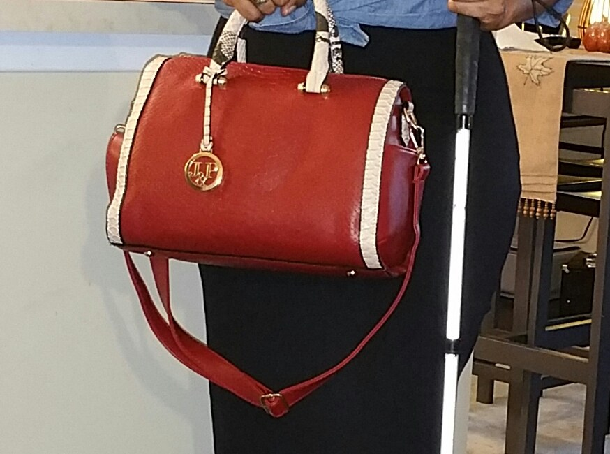 Close up photo of me holding the red barrel bag by the handles in my right hand while letting the adjustable strap hang. My white cane is in my left hand.