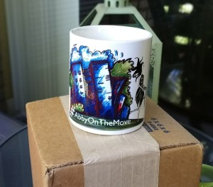 11 oz. Ceramic coffee mug with the #AbbyOnTheMove design centered on the front of the mug.