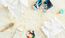 Baby shoes, bottle, teething ring, pacifier, clothes on a furry background
