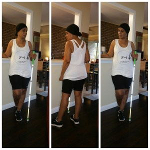 A triple photo collage of me standing, white cane in hand, wearing the tank, black shorts, black sneakers with white soles and black head wrap.