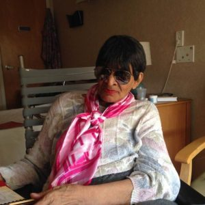 Picture of my mom at the nursing home sitting in her wheelchair. She's posing with her sunglasses and a colorful scarf tied around her neck.