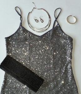 Silver sequined cami, black rhinestone embellished hard case clutch, silver necklace, earrings and bracelet accented with crystals.