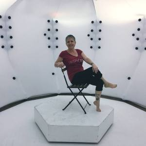 Picture of Libby Thaw posed seated on a chair with legs crossed in what looks like a white chamber.