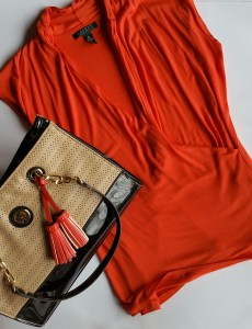 Orange top is described in the post. Tote bag is perforated faux leather panels on the front and back with black patent leather bottom and straps. Straps are connected to the bag with gold chain links and a gold medallion is on the front of the bag.