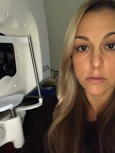 A picture of Nicole sitting in front of the angiogram machine. With an angiogram you put your head in a machine while one tech takes pictures and a different tech starts an IV in the arm with a solution that will light up Nicole's eyes so her doctor can get a better picture and idea of what is happening.