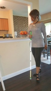 Posed standing next to my counter holding my white cane in my right hand.