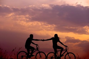 Two cyclists, one in front of the other. The person in front is reaching back with outstretched arm to the other cyclist against a rose colored sunset backdrop.