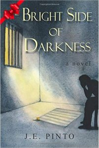 Bright Side of Darkness book cover illustrated as a corner room that has a bar covered window and light shining through. There is a silhouette of a person seated with their arms on their knees and head in their hands. In the upper left corner of the book is a bright red bow.
