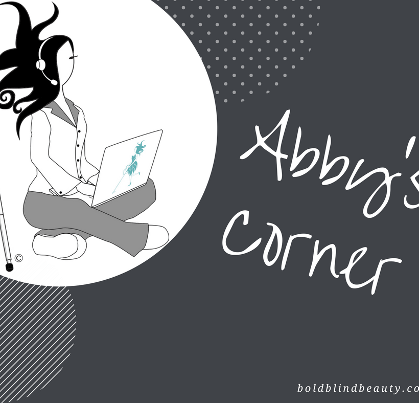 Abby is on the job sitting cross legged in her PJs (gray bottoms & white top with a gray collar) with a teal Abby logo laptop on her lap. Sporting her signature explosive hairstyle, she is wearing a headset with microphone and her white cane is propped up next to her.