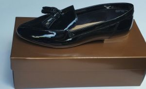 Brown shoe box with a black patent leather loafer with tassels on top of the box