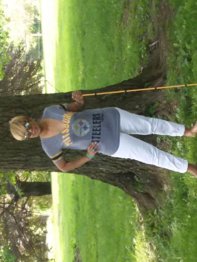 I'm standing in the grass in front of a tree with my color-coordinated (gold) white cane. My Steeler tee paired with white jeans and tan flats is a gray v-neck with black and gold team colors.