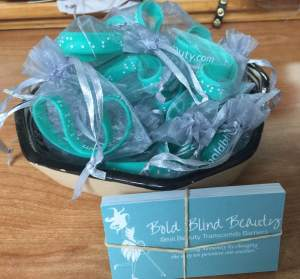 Teal and white braille Bold Blind Beauty silicon bracelets, each in its own mesh drawstring gift bag and Bold Blind Beauty business cards.