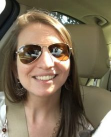 Recent picture of Virginia Maze sitting in a car smiling for the camera wearing Aviator sunglasses.