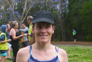 Photo of Megan looking very happy with herself immediately after aforementioned fabulous 5km. She is smiling for the camera wearing a black ball cap and tank in multiple shades of blue.