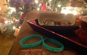 Image: In the foreground is a closeup of two teal Bold Blind Beauty braille bracelets sitting next to a red serving tray with an open eyeglass case on top of a table. In the background is beautiful lit Christmas tree.