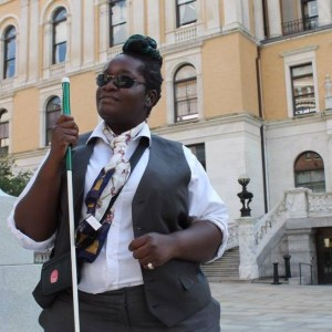 Casandra Xavier stands in front of the Massachusetts State house side entrance with her long Iowa cane in right hand with her braille display slung at her right side. She has a tent of green and blue dreadloacks carefully turned into a Bantu-knot Mohawk. Her hearing aid matches the color of her hair. Her eyes are shaded with frameless sunglasses. She wears a crisp white button down shirt with a Swedish grey vest and deep grey slacks. In the background is the side entrance of the house of reps in Boston displaying an awesome ancient structure. She posed for state house news reporter.
