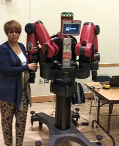 In this photo I am posing with the robot named Baxter. He sits on a gray base with wheels, has a black stand (body) and red arms. There is also a small screen where his face would be.