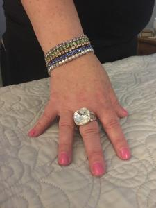 Melody is displaying some of her Touchstone Crystal. In the photo is her wrist and hand with a sparkly bracelet and ring.