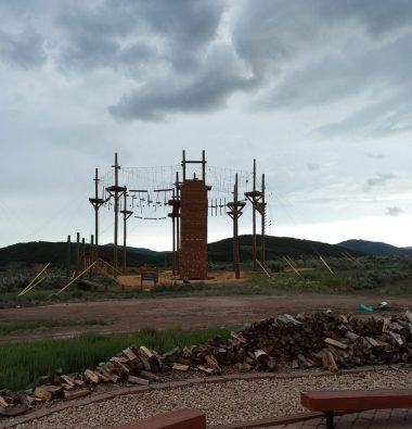 The Challenge Course beckons. In the foreground is benches around the fire pit